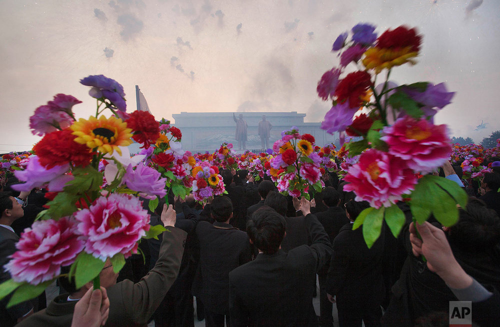 North Koreans wave artificial flowers at an unveiling ceremony for statues of the late leaders Kim Il Sung and Kim Jong Il in Pyongyang, North Korea, on April 13, 2012. (AP Photo/David Guttenfelder)