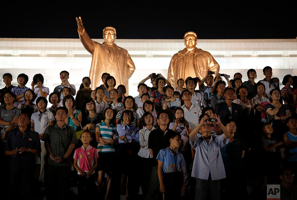 The bronze statues of late North Korean leaders Kim Il Sung and Kim Jong Il tower over people in Pyongyang as they watch fireworks explode on July 27, 2015, during a celebration of the 62nd anniversary of the armistice that halted the Korean War. (AP Photo/Wong Maye-E)