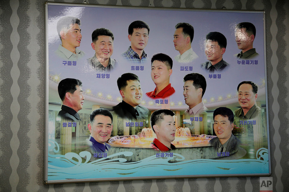 A poster showing different types of men's hair styles hangs outside a barber shop at the Munsu water park in Pyongyang, North Korea, on Dec. 1, 2015. (AP Photo/Wong Maye-E)