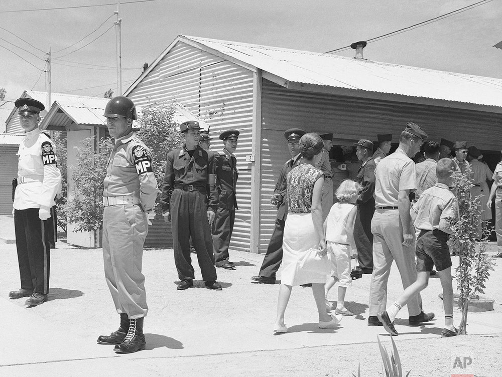 Walking past United Nations and North Korean guards on duty, sightseers flock around the building in which the Military Armistice Commission meets in the Demilitarized Zone at Panmunjom, Korea, on July 8, 1963. (AP Photo/KIM)
