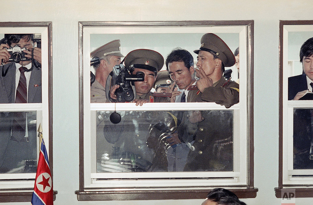 A North Korean army officer films through a window at a meeting of the Military Armistice Commission in Seoul, South Korea, on Sept. 12, 1989, as other communist officials listen. (AP Photo/Yun Jai-Hyoung)