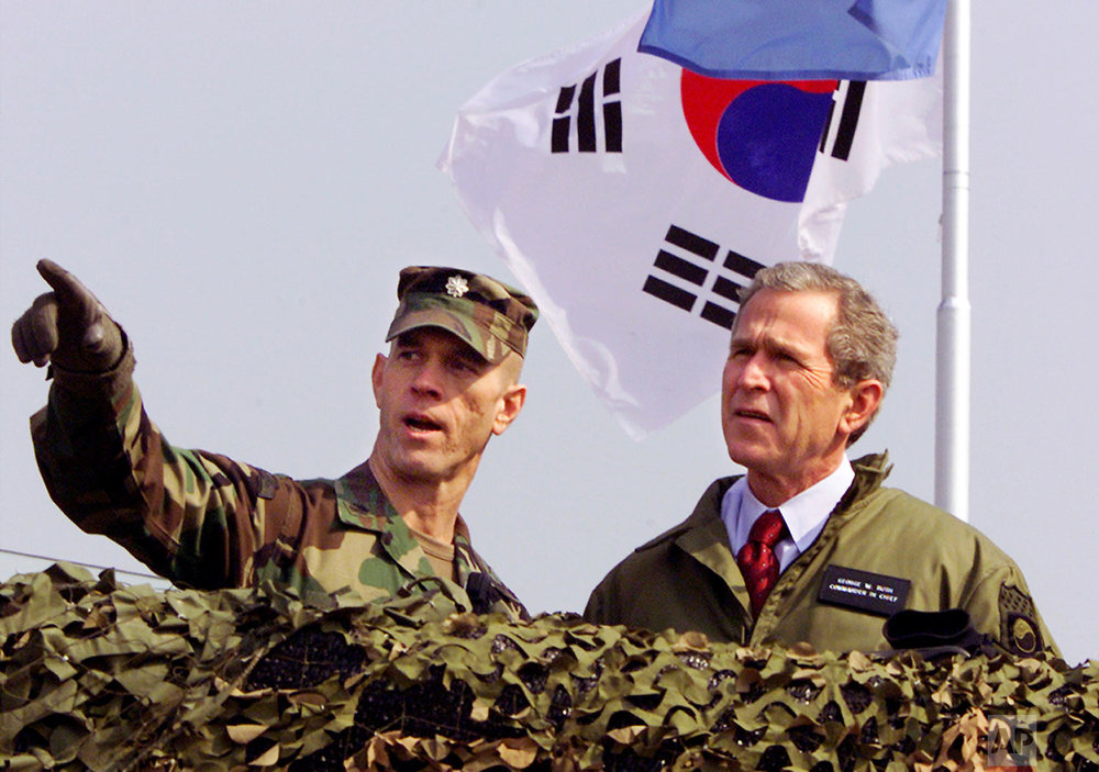 """U.S. President George W. Bush, right, looks out at North Korea from Observation Point Ouellette in the Demilitarized Zone, the tense military border between the two Koreas, in Panmunjom, Korea, on Feb. 20, 2002. Bush's visit to the DMZ came a few weeks after he labeled North Korea part of an """"axis of evil."""" (AP Photo/J. Scott Applewhite)"""