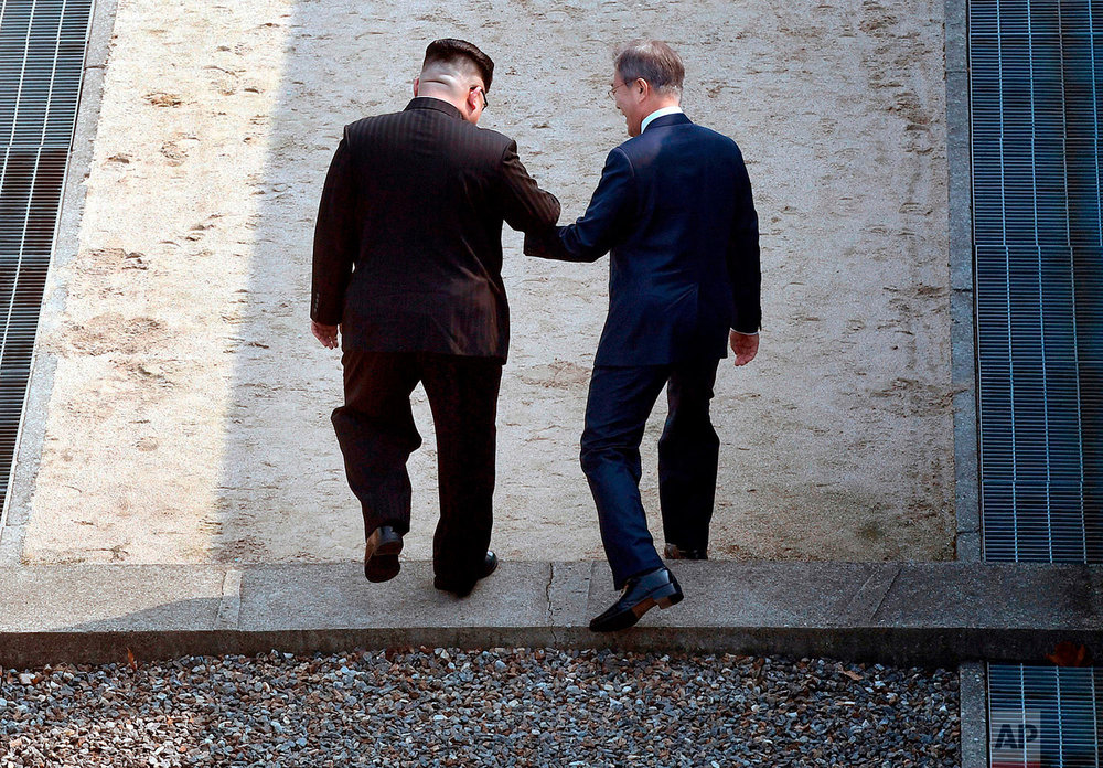 North Korean leader Kim Jong Un, left, and South Korean President Moon Jae-in cross the military demarcation line at the border village of Panmunjom in the Demilitarized Zone that divides the North and South on April 27, 2018. (Korea Summit Press Pool via AP)
