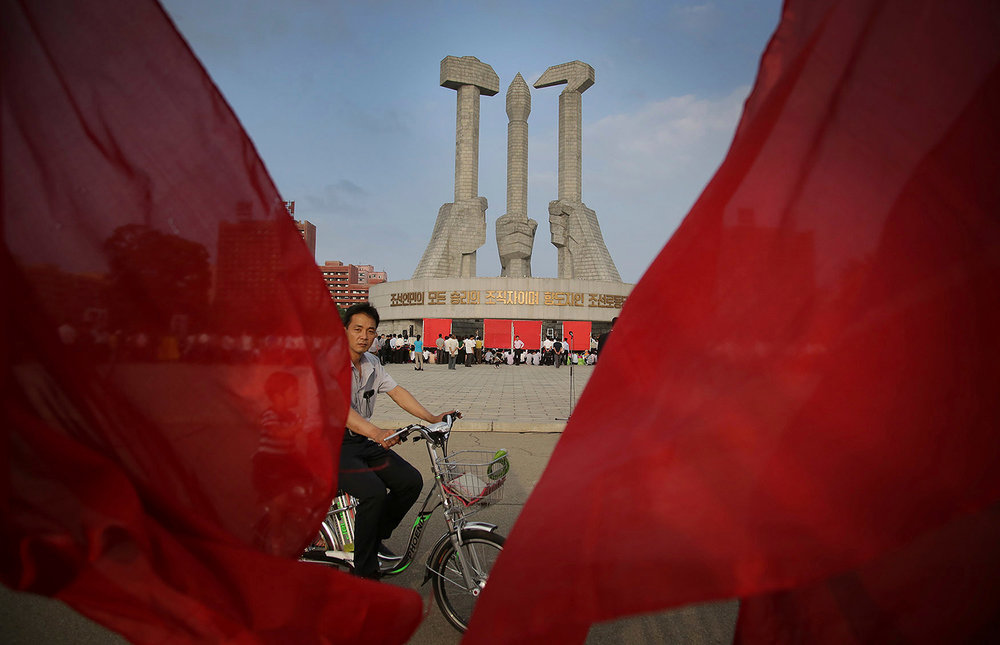 A man framed by red party flags cycles past the Workers' Party monument in Pyongyang, North Korea, on June 19, 2016, the day North Koreans celebrate former leader Kim Jong Il's 1964 entry into the Central Committee of the Workers' Party of Korea. (AP Photo/Wong Maye-E)