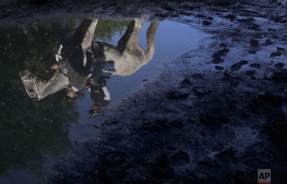 A thoroughbred, its trainer and exercise rider are reflected in a mud puddle as they walk back to the stable after a workout at Belmont Park, Tuesday, June 5, 2018, in Elmont, N.Y. Justify will attempt to become the 13th Triple Crown winner when he runs in the 150th running of the Belmont Stakes horse race on Saturday. (AP Photo/Julie Jacobson)