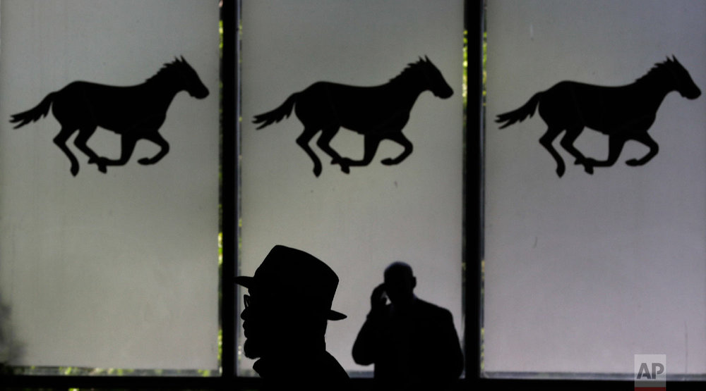 Horse racing fans walk through the grandstand before the 150th running of the Belmont Stakes horse race, Saturday, June 9, 2018, in Elmont, N.Y. (AP Photo/Frank Franklin II)
