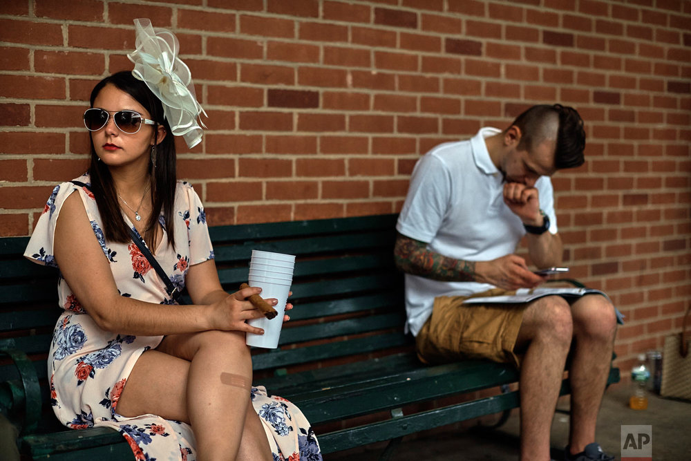 Horse racing spectators take a break from festivities before the 150th running of the Belmont Stakes horse race, Saturday, June 9, 2018, in Elmont, N.Y. (AP Photo/Andres Kudacki)