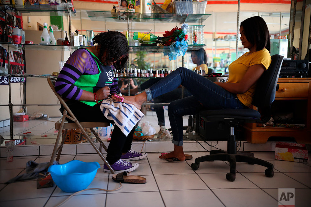 Marie Toussaint gives a pedicure to a customer at her local beauty salon in downtown Tijuana, Mexico, May 5, 2018. (AP Photo/Emilio Espejel)