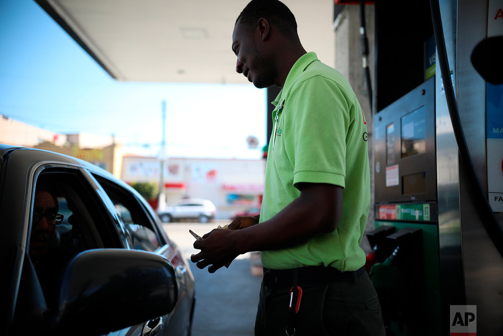 Herllain Gamin, a Haitian migrant, counts his change at the gas station where he works in downtown Tijuana, Mexico, May 4, 2018. When he first arrived, Gamin said that he experienced racist attitudes from Mexicans, but now says he and others are accepted and welcomed by most. (AP Photo/Emilio Espejel)