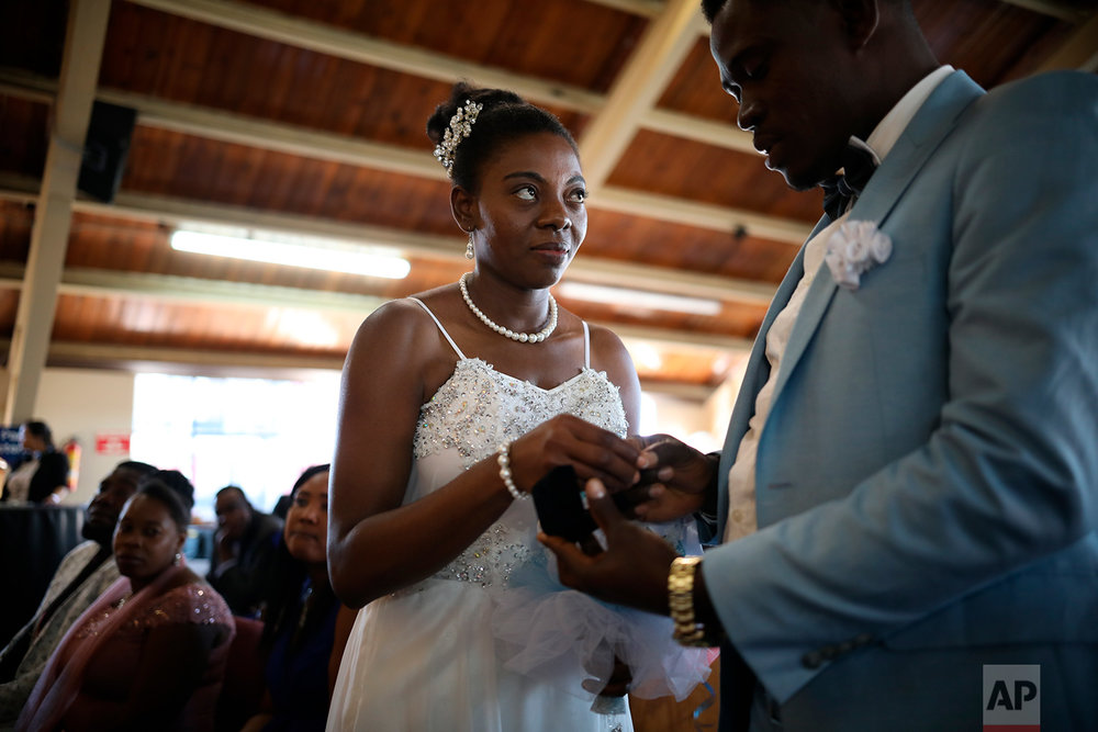 A bride exchanges vows during a mass wedding held at the First Baptist Church of Tijuana, Mexico, May 5, 2018. Eighteen couples, all of them Haitian migrants, were married at the ceremony. (AP Photo/ Emilio Espejel)