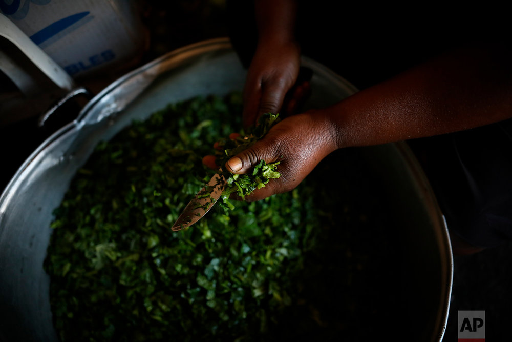 Rosaline, a Haitian migrant, cuts spinach for a dish at her restaurant in downtown Tijuana, Mexico, May 4, 2018. (AP Photo/Emilio Espejel)