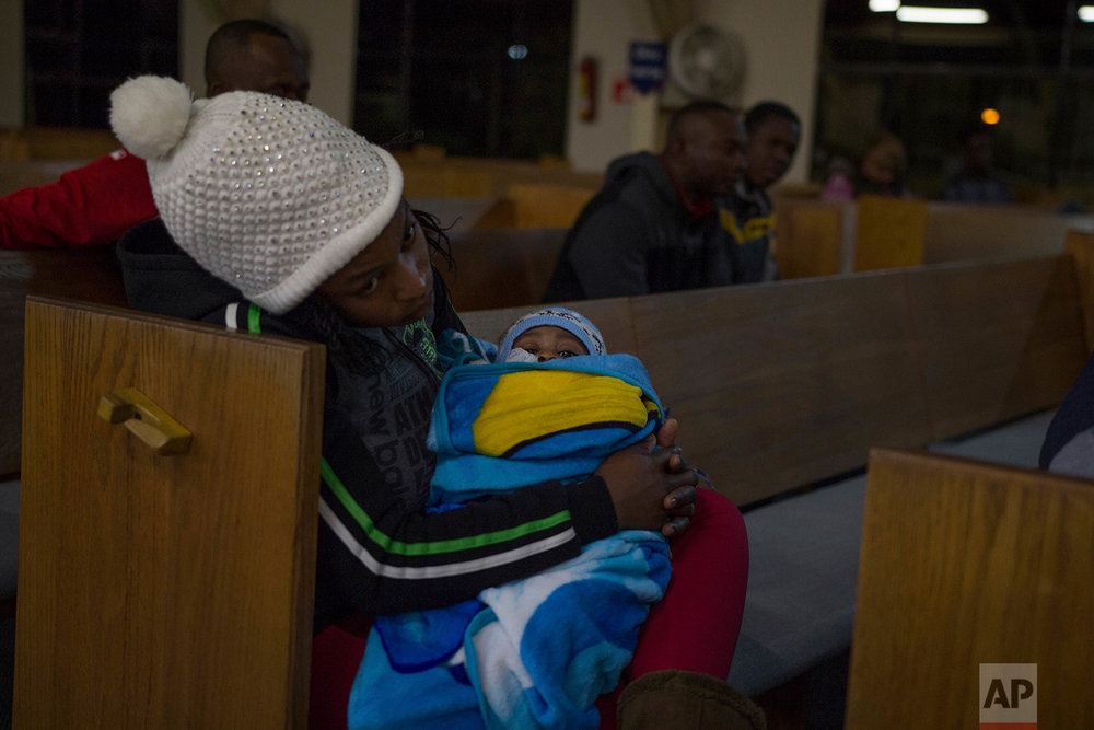 A woman holds her baby during a service at The First Baptist Church of Tijuana in Mexico, Feb. 26, 2018. The church is located in downtown Tijuana and forms an important part of Haitian community life in the city. (AP Photo/Emilio Espejel)