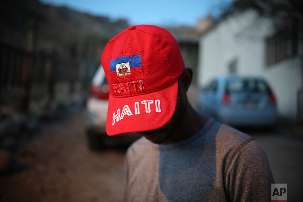 Pierre Franzzi shows off a red cap with his country's flag emblazoned on it outside the Ambassadors of Jesus Church in Tijuana, Mexico, May 4, 2018. (AP Photo/Emilio Espejel)