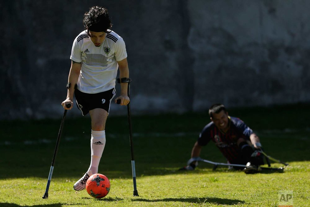 In this June 9, 2018 photo, David Arguello of the Android soccer club controls the ball while balancing himself with crutches, at a match against Fuerzas Armadas during a national soccer tournament for players with amputated limbs, in Quito, Ecuador. One-legged soccer was started in the early 1980s by Don Bennett, an active sportsman from Seattle who lost his leg in a boating accident, according to the American Amputee Soccer Association. (AP Photo/Dolores Ochoa)