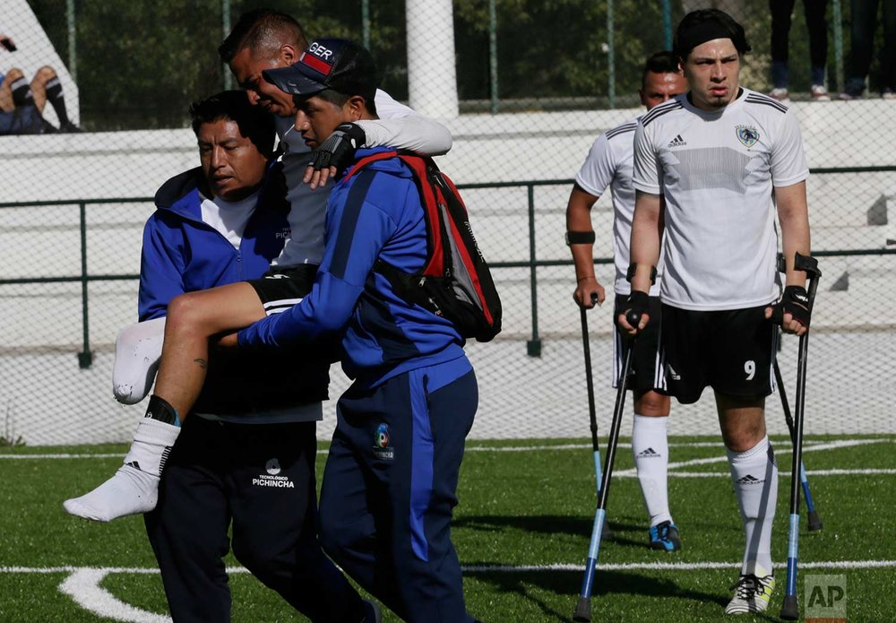 In this June 10, 2018 photo, Wilson Tianga of the Android team is carried off the field after an injury, during a game against Fuerzas Armadas as part of the national soccer tournament for players with amputated limbs, in Quito, Ecuador. Six teams comprising of 72 players, including two women, competed at the tournament and was won this year by Android. (AP Photo/Dolores Ochoa)