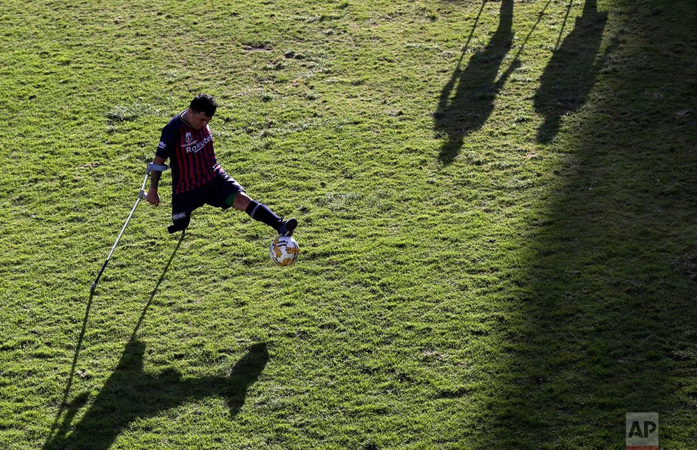 In this June 9, 2018 photo, Robin Burbano controls the ball as he balances himself on crutches, during a game against El Empalme as part of the national soccer tournament for players with amputated limbs, in Quito, Ecuador. It's the South American nation's second amputee soccer tournament, while the country's national team didn't qualify for the FIFA World Cup beginning this month in Russia. (AP Photo/Dolores Ochoa)