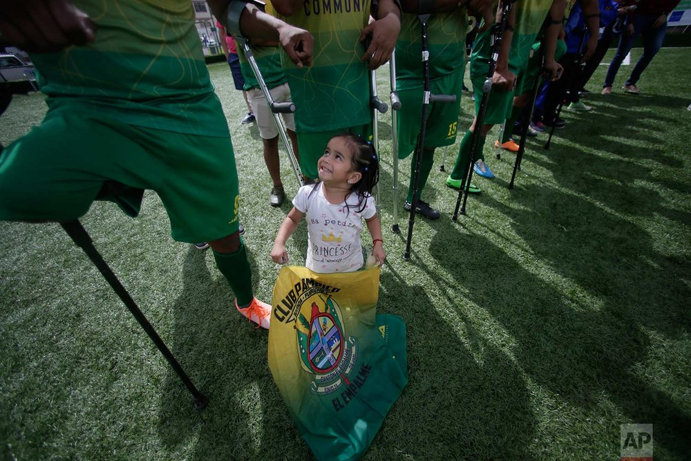 """In this June 10, 2018 photo, a young fan of the El Empalme team stands with players after they won the the national soccer tournament for players with amputated limbs, in Quito, Ecuador. """"I want to show the world I can be the Messi of the amputees,"""" said Holger Velez, 28, a player for El Empalme. (AP Photo/Dolores Ochoa)"""