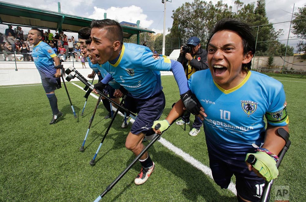 In this June 10, 2018 photo, Android team players celebrate winning the national soccer tournament for players with amputated limbs, in Quito, Ecuador. While the one-legged game is just taking off in Ecuador, it's getting a big boost from the country's president, Lenin Moreno, a wheelchair-bound paraplegic who was a major force for the rights of the disabled around the world as the United Nations' envoy on disability and accessibility in Geneva, Switzerland between 2013 and 2016. (AP Photo/Dolores Ochoa)