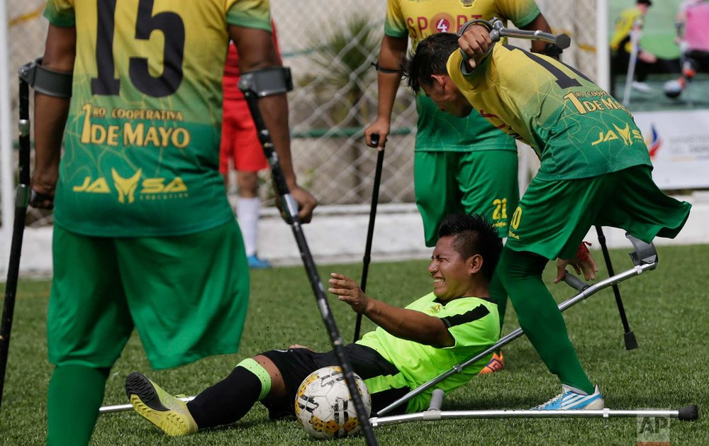 In this June 10, 2018 photo, Blas Ruiz falls on the pitch after he was fouled by the El Empalme team during a national soccer tournament for players with amputated limbs, in Quito, Ecuador. Some of the players competing at the tournament in Ecuador are hoping to be selected for a national team that will compete in the 15th World Amputee Football Federation's World Cup taking place later this year in Guadalajara, Mexico. (AP Photo/Dolores Ochoa)