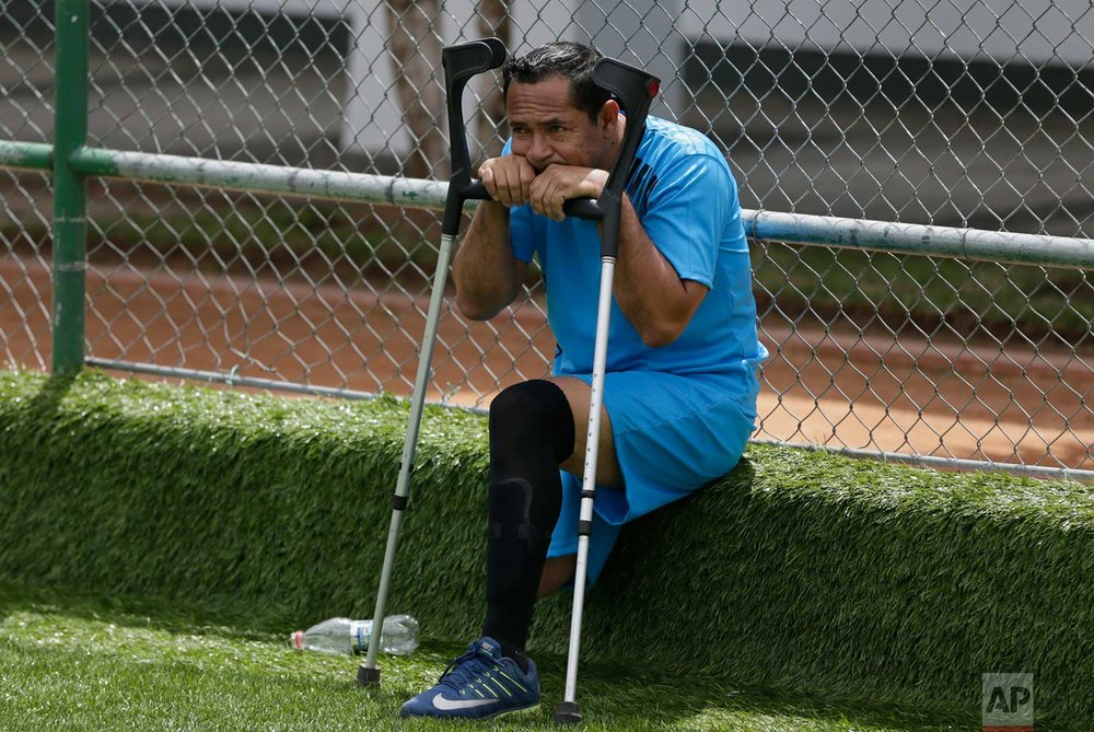 In this June 8, 2018 photo, Edison Rivas, member of the Manta Club, sits dejected after his team was defeated by Fuerzas Armadas at the national soccer tournament for players with amputated limbs, in Quito, Ecuador. While the one-legged game is just taking off in Ecuador, it's getting a big boost from the country's president, Lenin Moreno, a wheelchair-bound paraplegic who was a major force for the rights of the disabled around the world as the United Nations' envoy on disability and accessibility in Geneva, Switzerland between 2013 and 2016. (AP Photo/Dolores Ochoa)