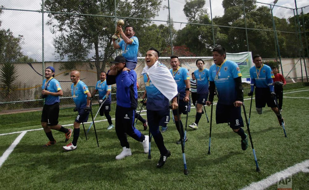 In this June 10 photo, members of the Android soccer team celebrate with their trophy after winning the championship game of a national tournament for players with amputated limbs, in Quito, Ecuador. One-legged soccer was started in the early 1980s in Seattle and today is played in 40 countries around the world. (AP Photo/Dolores Ochoa)