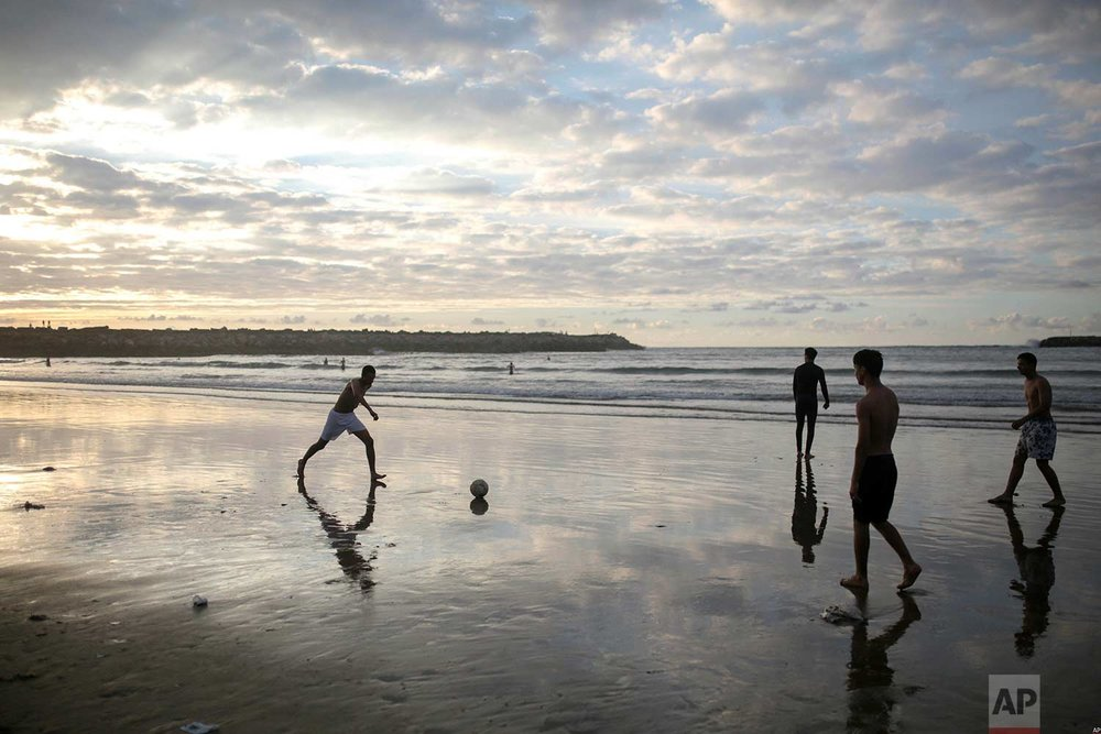 In this photo taken on Saturday, June 9, 2018, boys are silhouetted against the sunset light as they play football on the beach, minutes before breaking their fast in the holy month of Ramadan, in Rabat, Morocco. (AP Photo/Mosa'ab Elshamy)