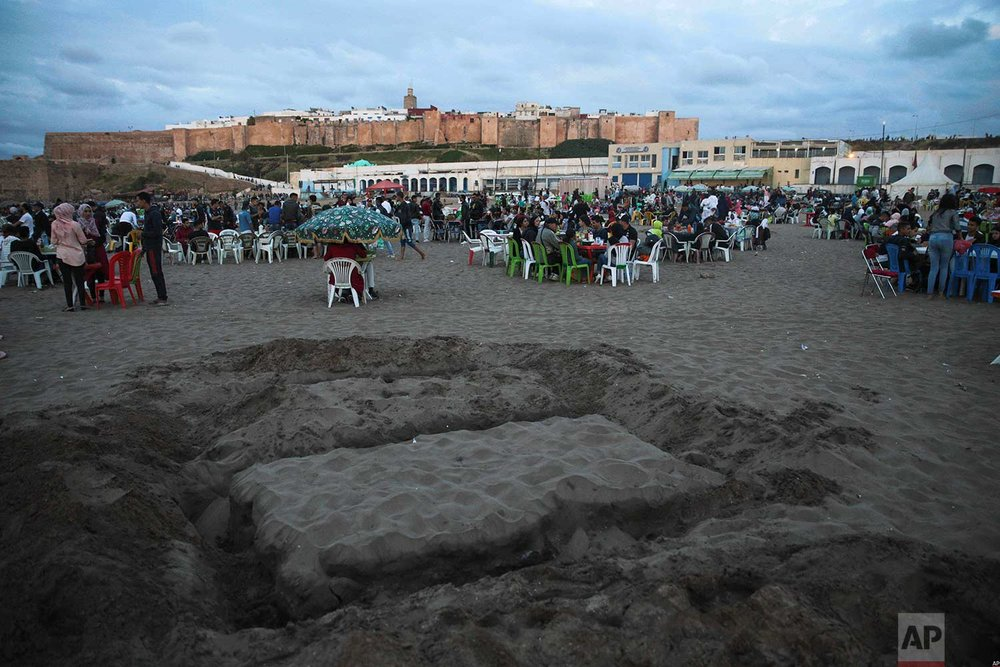A table made of sand is prepared for friends and families to use to break their fast on the beach in the holy month of Ramadan, in Rabat, Morocco, Saturday, June 9, 2018. (AP Photo/Mosa'ab Elshamy)
