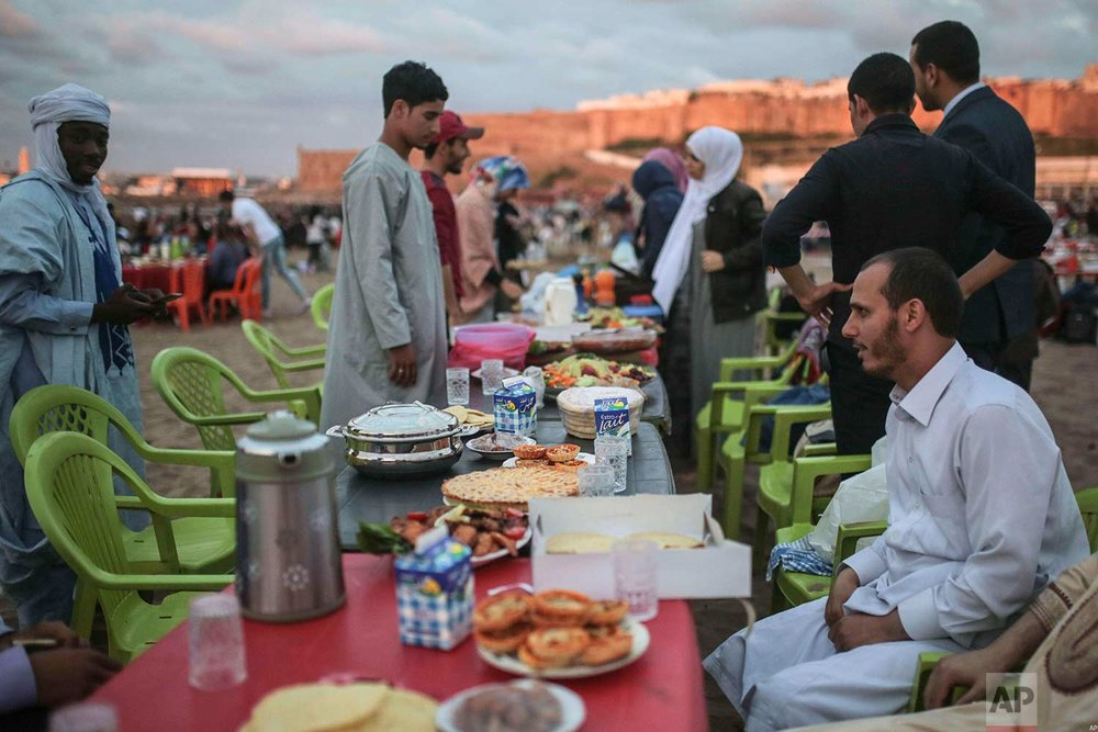 People wait to break their fast on the beach in the holy month of Ramadan, in Rabat, Morocco, Saturday, June 9, 2018. (AP Photo/Mosa'ab Elshamy)