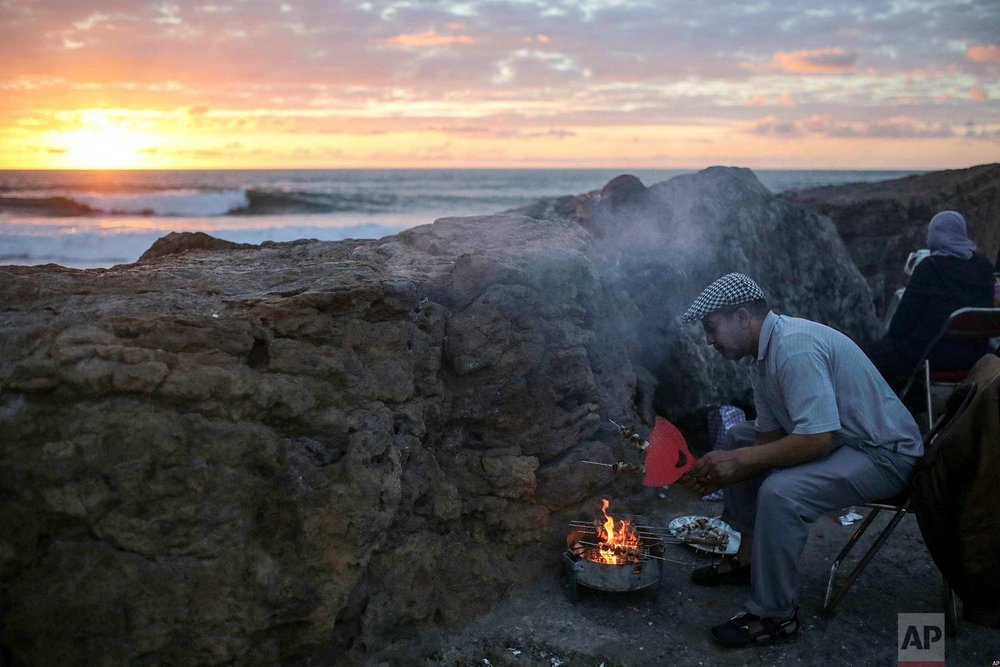 A man grills meat for his family on the beach to break their fast the holy month of Ramadan, in Rabat, Morocco, Saturday, June 9, 2018. (AP Photo/Mosa'ab Elshamy)