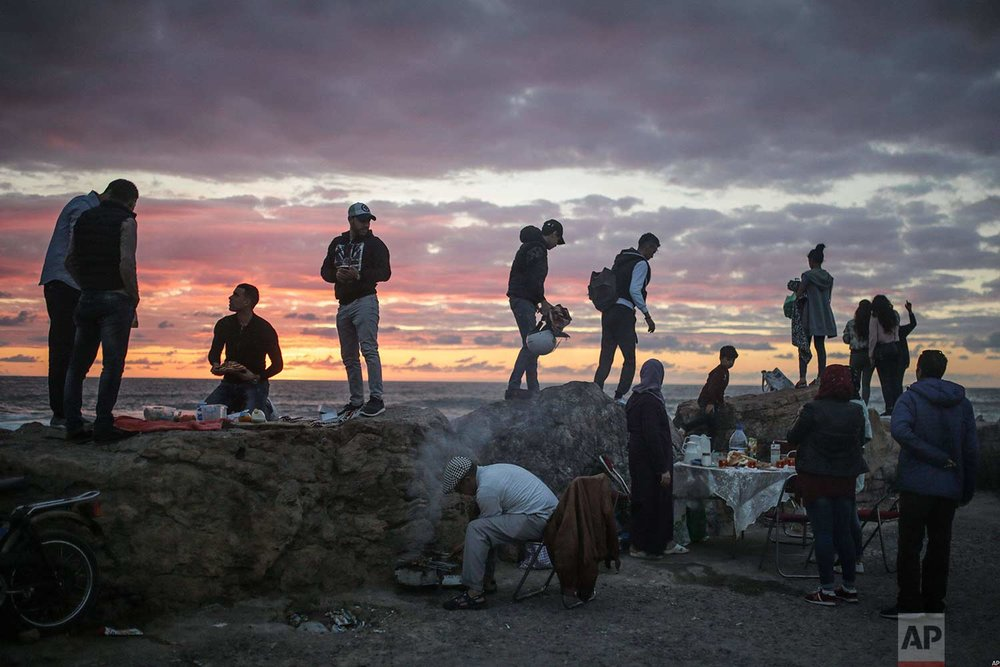 Beachgoers observe the sunset as a man grills meat for his family to break their fast in the holy month of Ramadan, Rabat, Morocco, Saturday, June 9, 2018. (AP Photo/Mosa'ab Elshamy)