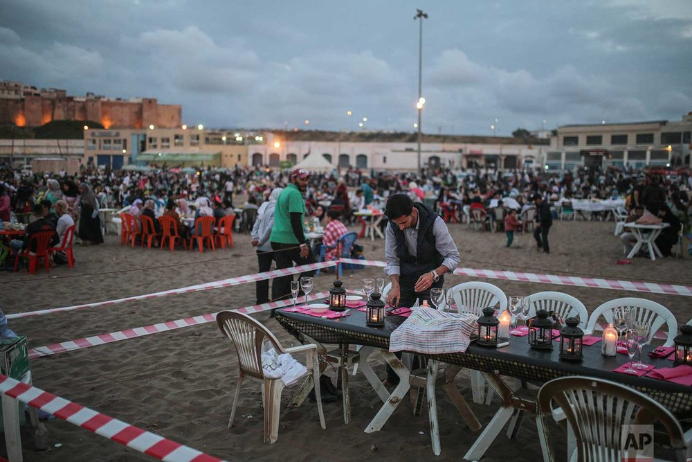 A man prepares a table for beachgoers to break their fast in the holy month of Ramadan, in Rabat, Morocco, Saturday, June 9, 2018. (AP Photo/Mosa'ab Elshamy)