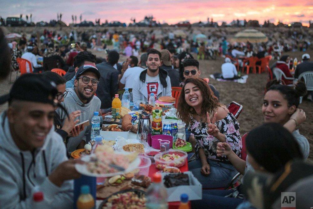 Friends pose for a photo as they prepare to break their fast on the beach in the holy month of Ramadan, on Rabat beach, Morocco, Saturday, June 9, 2018. (AP Photo/Mosa'ab Elshamy)