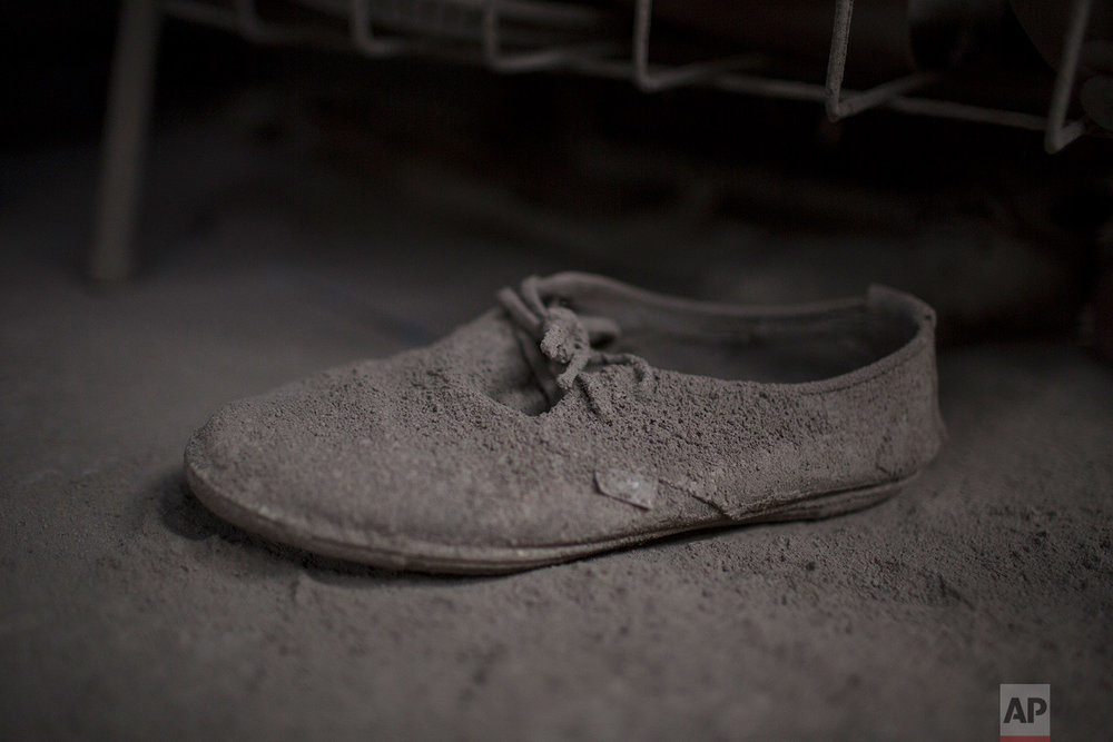 This June 9, 2018 photo shows a shoe caked with volcanic ash spewed by the Volcan de Fuego or Volcano of Fire, inside a home in San Miguel Los Lotes, Guatemala. (AP Photo/Rodrigo Abd)