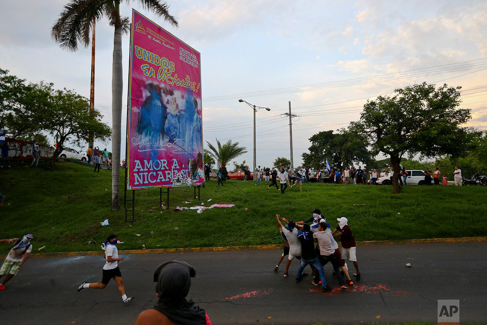 "In this May 20, 2018 photo, anti-government protesters work to pull down a government billboard announcing the Spanish message ""United in victory! Love for Nicaragua,"" in Managua, Nicaragua. (AP Photo/Esteban Felix)"