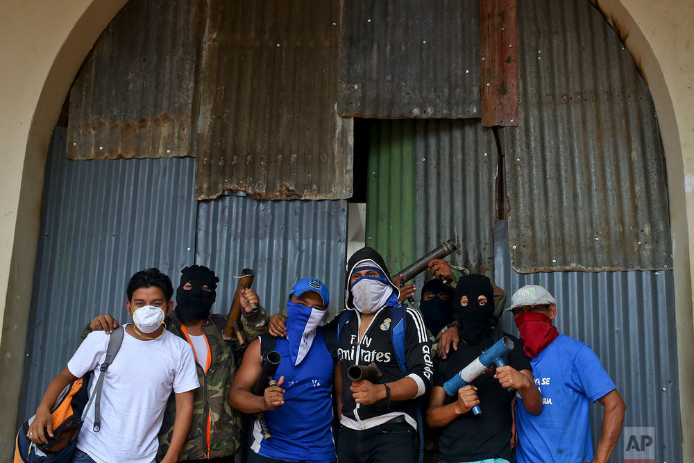 In this May 28, 2018 photo, masked protesters pose for a group photo holding their homemade mortars, outside a shopping center with a store covered by metal sheeting to protect it from looting, in Masaya, Nicaragua. (AP Photo/Esteban Felix)