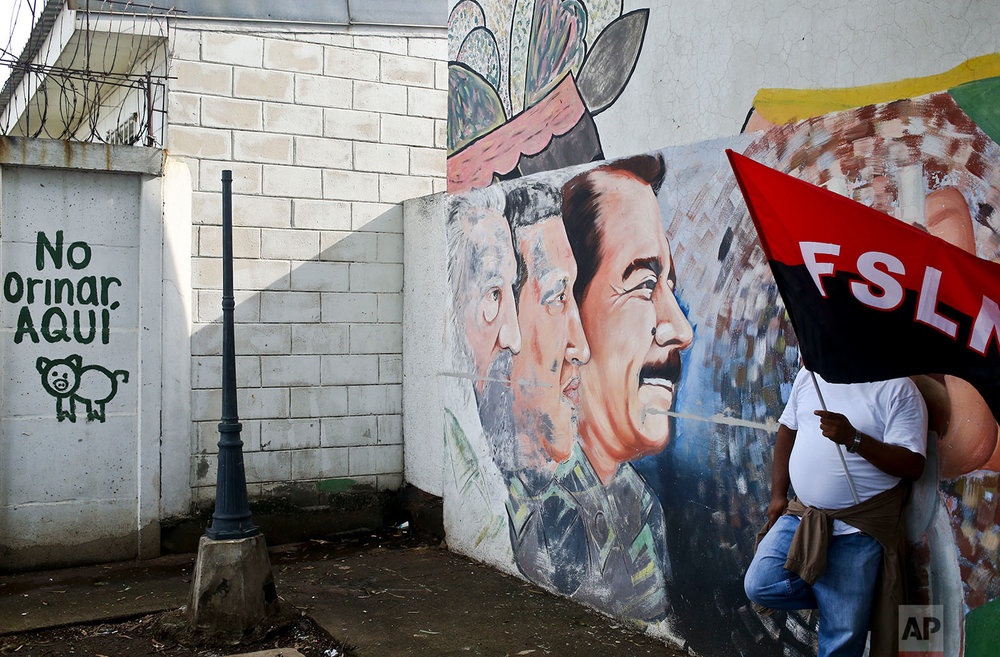 In this May 26, 2018 photo, a government supporter holds a Sandinista flag by a mural featuring Nicaragua's President Daniel Ortega, Venezuela's late President Hugo Chavez, and Cuba's late leader Fidel Castro, during government event in Managua, Nicaragua.  (AP Photo/Esteban Felix)