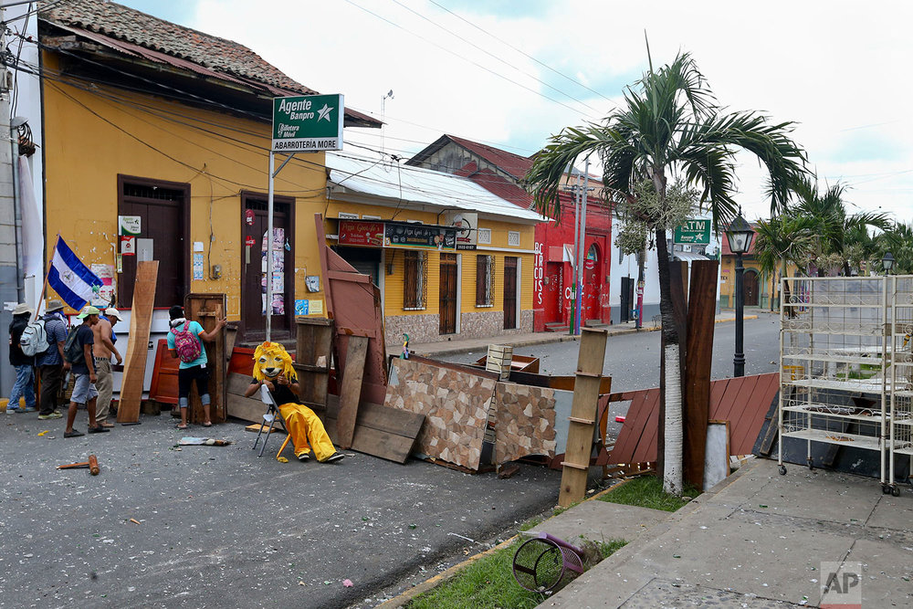 "In this June 2, 2018 photo, an anti-government protester dressed in a lion costume to hide his identity sits at a barricade during clashes with police in Masaya, Nicaragua. The lion costume is normally used in this town during a traditional dance called ""Los Diablitos,"" or The Devils, in honor of Saint Jeronimo at the end of November. (AP Photo/Esteban Felix)"