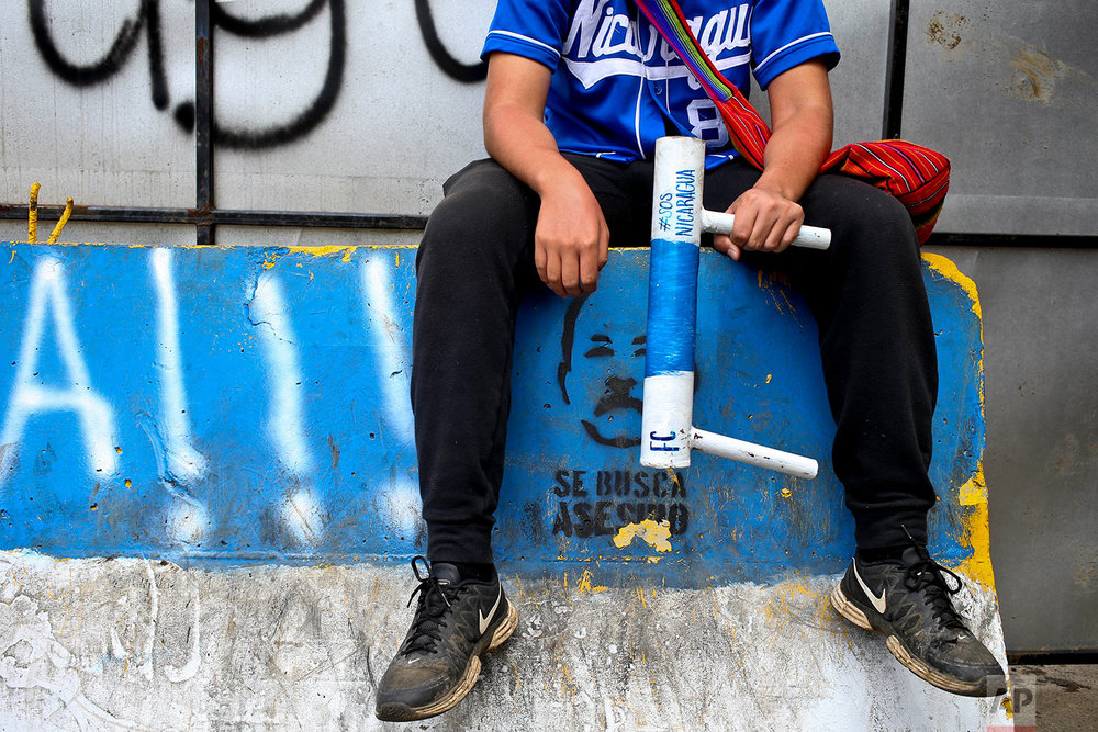 In this June 6, 2018 photo, an anti-government protester holds a handmade mortar at a roadblock in Ticuantepe, Nicaragua. (AP Photo/Esteban Felix)