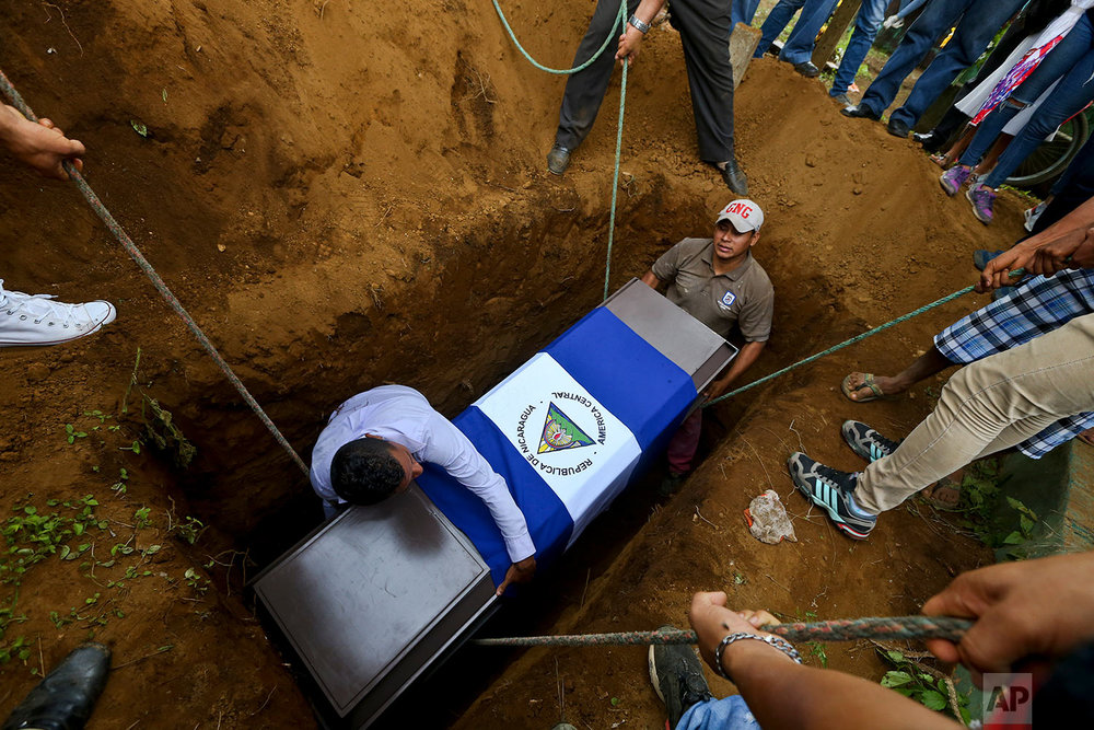 In this May 25, 2018 photo, people lower the coffin of Manuel de Jesus Chavez, 38, at the cemetery in Leon, Nicaragua. Chavez, 38, died during clashes with police as anti-government protesters blocked the Panamerican Highway. (AP Photo/Esteban Felix)