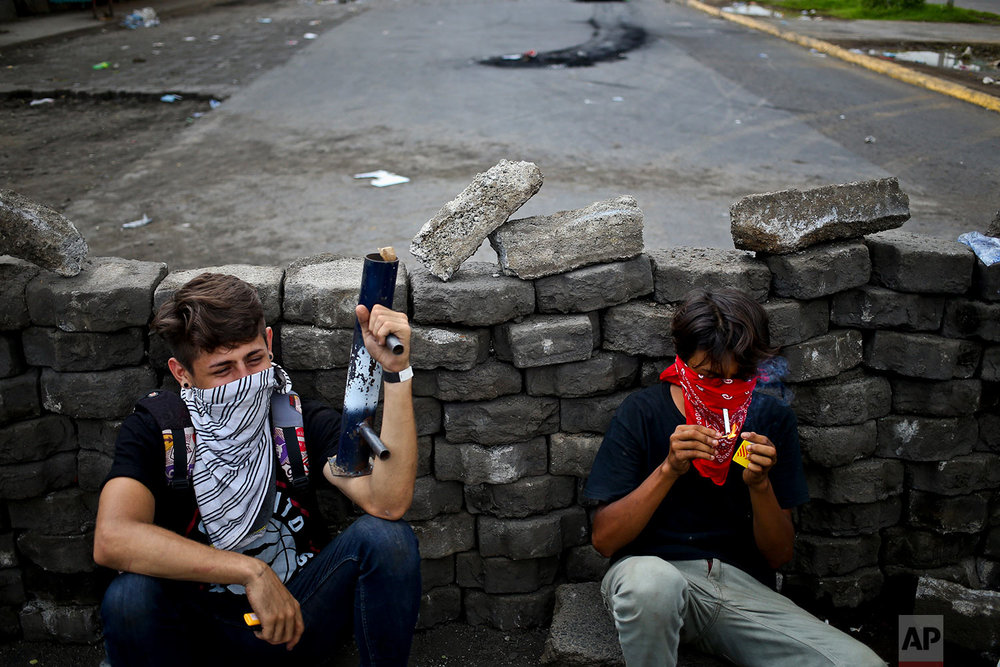 In this May 31, 2018 photo, young anti-government protesters squat behind a roadblock they set up near the Supreme Electoral Council, one holding his homemade mortar in Managua, Nicaragua. (AP Photo/Esteban Felix)
