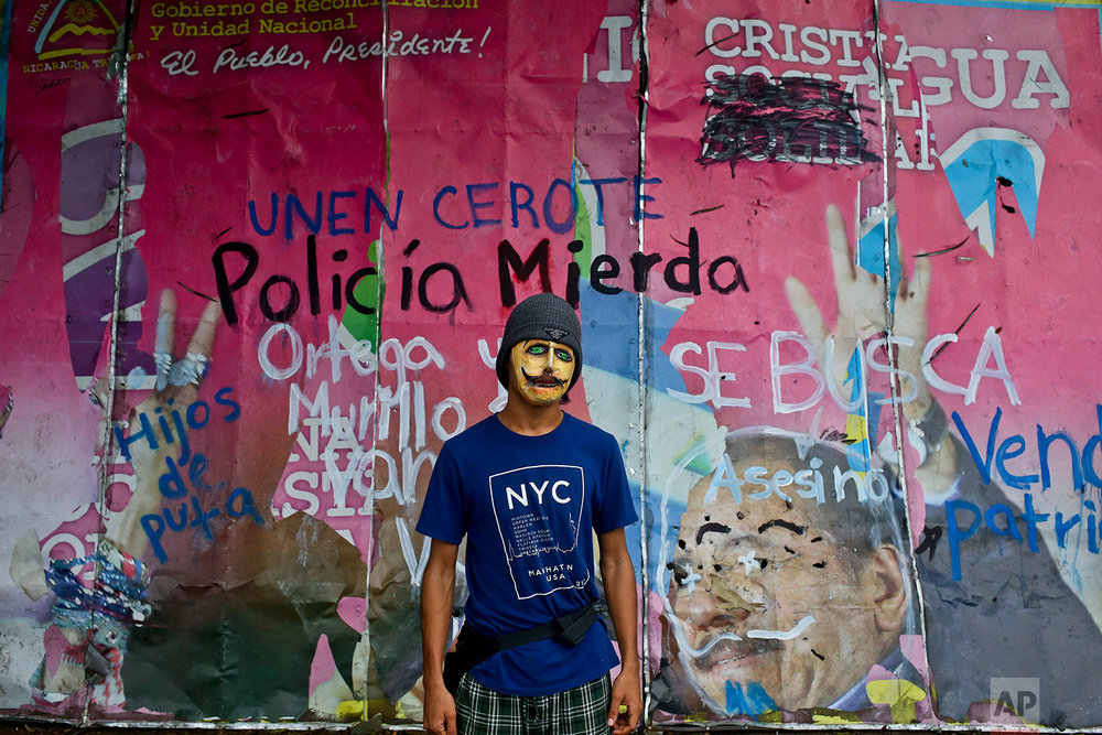 In this May 20, 2018 photo, a university student poses for a picture wearing a mask to hide his identity, in front a defaced billboard of Nicaragua¥s President Daniel Ortega and his wife, first lady Rosario Murillo, outside the Agrarian University in Managua, Nicaragua.  (AP Photo/Esteban Felix)