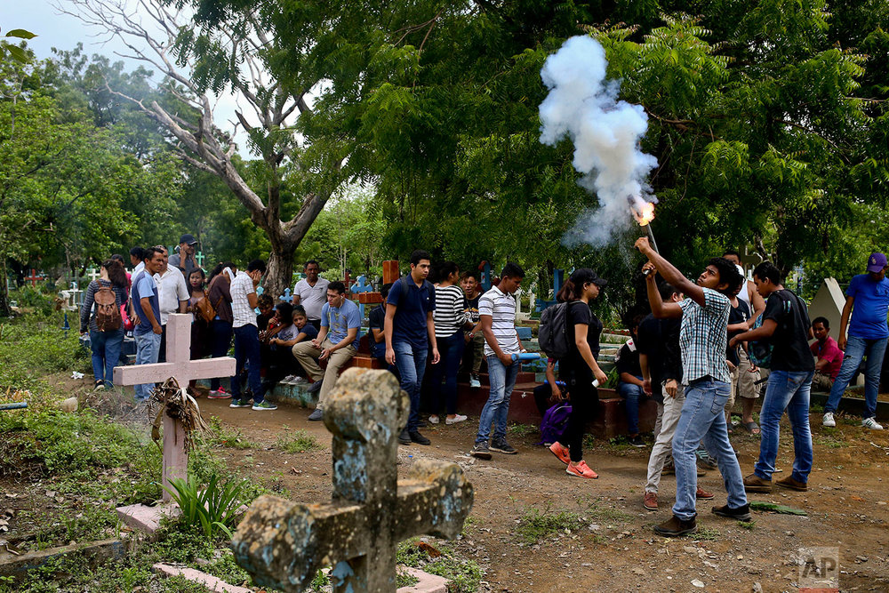In this May 25, 2018 photo, a youth fires a handmade mortar during the burial of Manuel de Jesus Chavez at the cemetery in Leon, Nicaragua. Chavez, 38, died during clashes with police as anti-government protesters blocked the Panamerican Highway. (AP Photo/Esteban Felix)