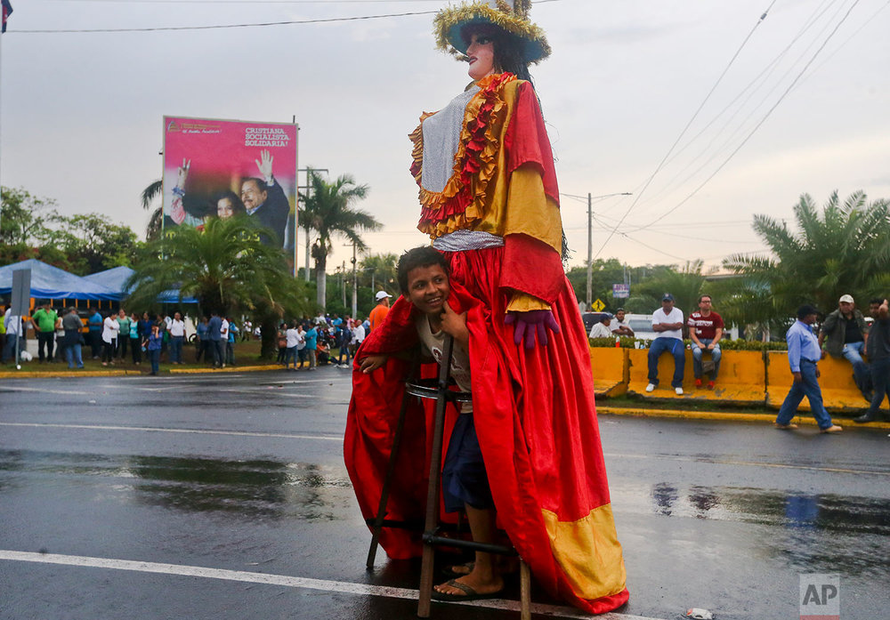 "In this May 22, 2018 photo, a youth peers from under a large doll coined ""La Gigantona,"" or The Gigantic, during a pro-government event in Managua, Nicaragua, where a billboard stands behind of President Daniel Ortega and his wife, Vice President Rosario Murillo. (AP Photo/Esteban Felix)"