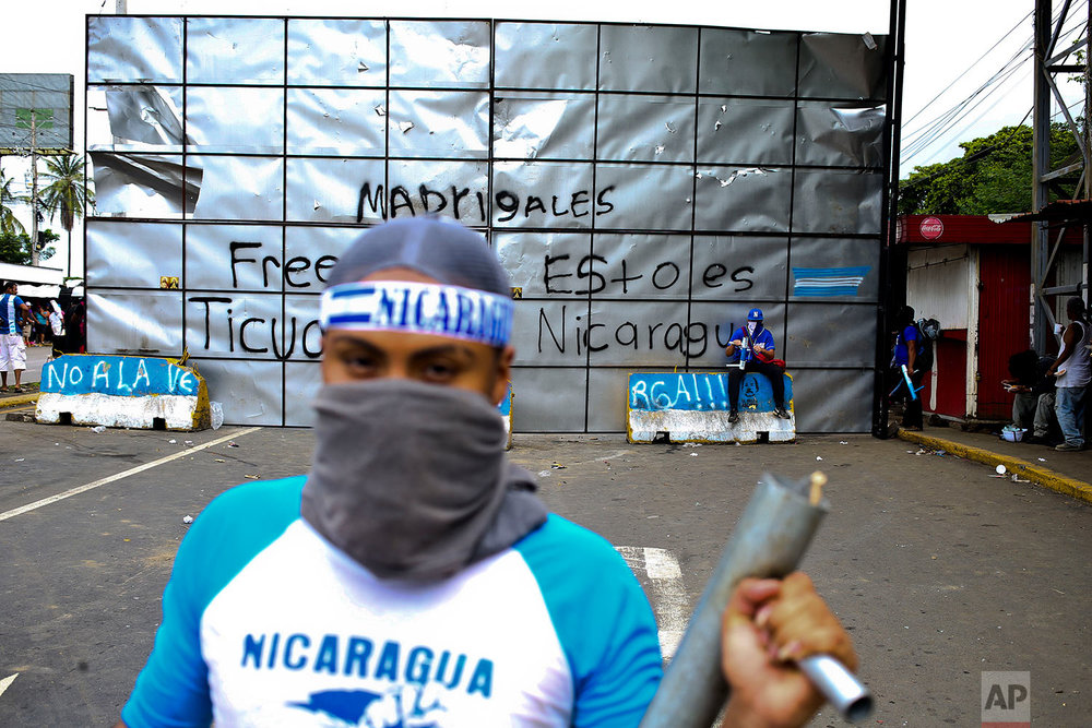 In this June 6, 2018 photo, an anti-government protester poses for a picture holding a homemade mortar at a roadblock set up by protesters in Ticuantepe, Nicaragua. (AP Photo/Esteban Felix)