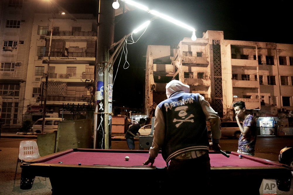 Youth play pool on a street in front of damaged buildings due to the war. (AP Photo/Nariman El-Mofty)