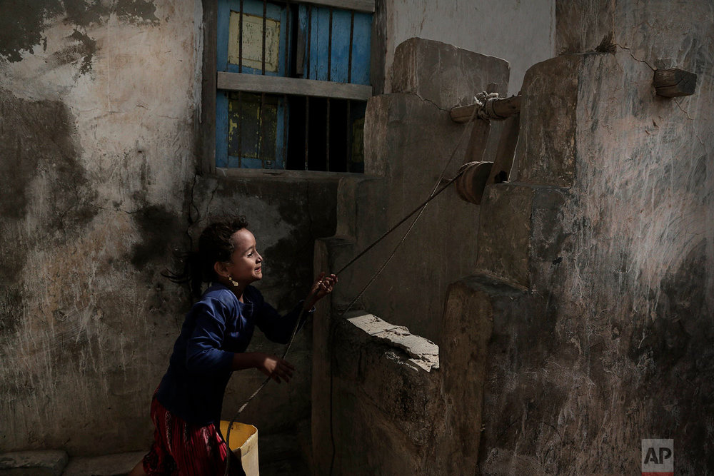 A girl pulls water from a well in the home of Ahmed al-Kawkabani, leader of the southern resistance unit in Hodeida, in al-Khoukha, Yemen. (AP Photo/Nariman El-Mofty)