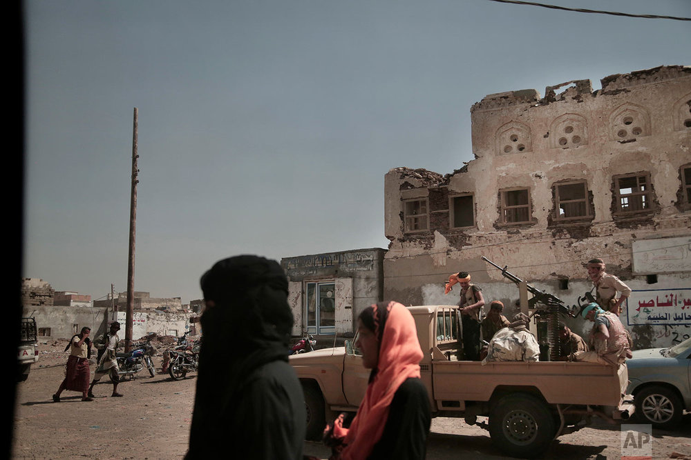 Women walk past Saudi-led coalition backed forces, leading the campaign to take over Hodeida, as they patrol Mocha, a port city on the Red Sea coast of Yemen.(AP Photo/Nariman El-Mofty)