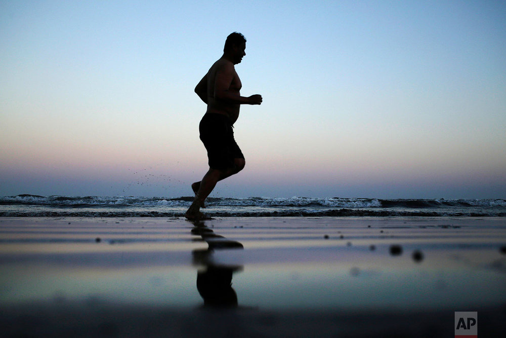 In this Feb. 13, 2018, photo, a man jogs on the beach after the sun sets in Aden, Yemen. (AP Photo/Nariman El-Mofty)