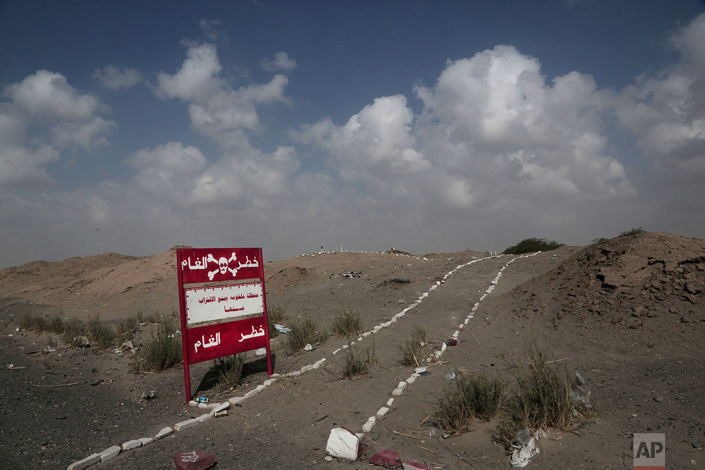 """A sign with Arabic that reads, """"danger mines, danger mines"""" on the highway from Abyan to Aden in Yemen. (AP Photo/Nariman El-Mofty)"""