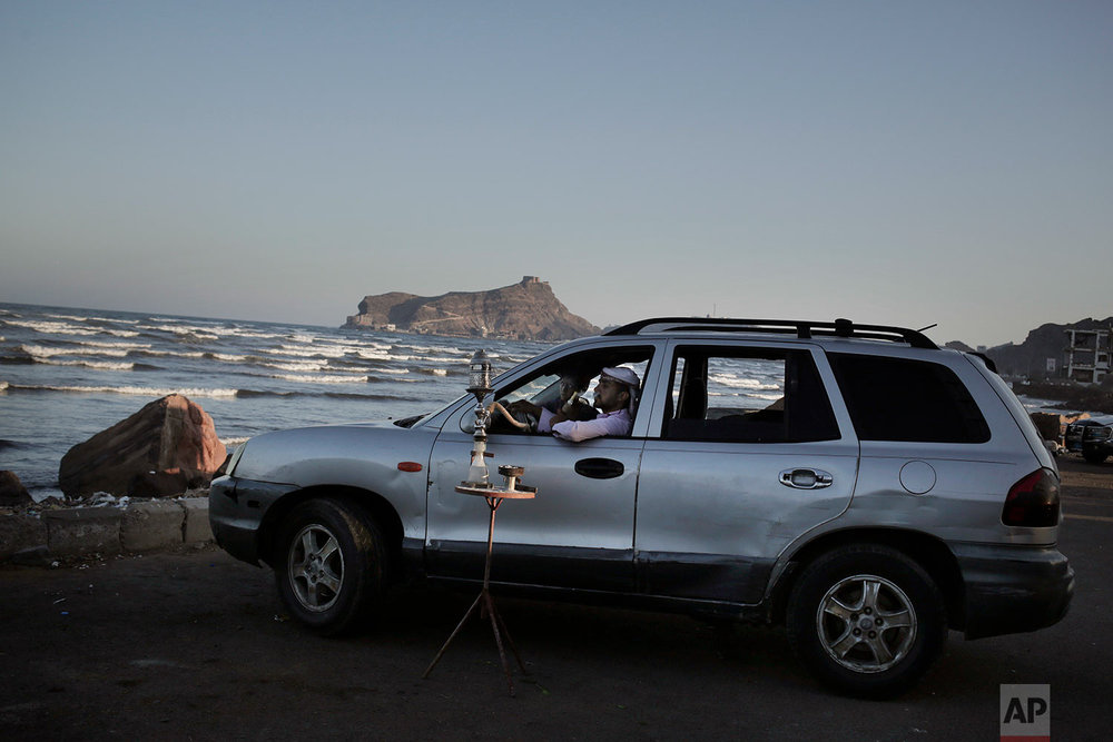 "A man smokes a traditional ""shisha"" water pipe inside his car parked his car in front of the beach in Aden, Yemen. (AP Photo/Nariman El-Mofty)"